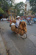 Old Town, tourists on cyclos and woman selling traditional hats and baskets from her bicycle.