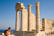Tourists next to the columns of a ruined temple at the Acropolis, Lindos, Rhodes, Dodecanese Islands, Greece