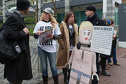 © Licensed to London News Pictures. 26/02/2013. London, UK. 'No More Page 3' campaigners collect signatures for a petition with a spoof female Lego model outside The Sun's News International offices in Wapping, East London on 26 February 2013. Demonstrators are calling for Rupert Murdoch to end topless female models in The Sun newspaper, claiming it is unsuitable for family reading and are using a spoof Lego model, nicknamed 'Leanne' as a campaign tool to target the joint promotion running this week between corporate advertisers, Lego and The Sun which is offering free Lego toys aimed at children. Photo credit : Vickie Flores/LNP