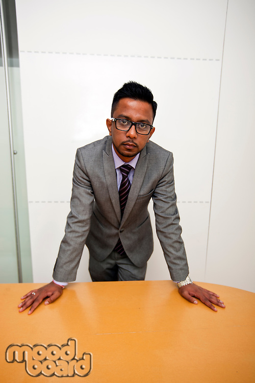 Portrait of Indian Businessman wearing glasses with hands on the table