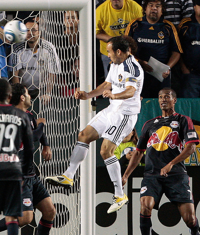 Los Angeles Galaxy forward Landon Donovan, center, heads the ball into the net as New York Red Bulls defender Roy Miller, right, of Costa Rica looks on during the first half of a MLS soccer match, Saturday, May 7, 2011, in Carson, Calif. (AP Photo/Jason Redmond)