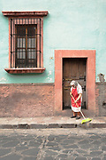 Woman in colorful apron does morning sweeping in San Miguel de Allende