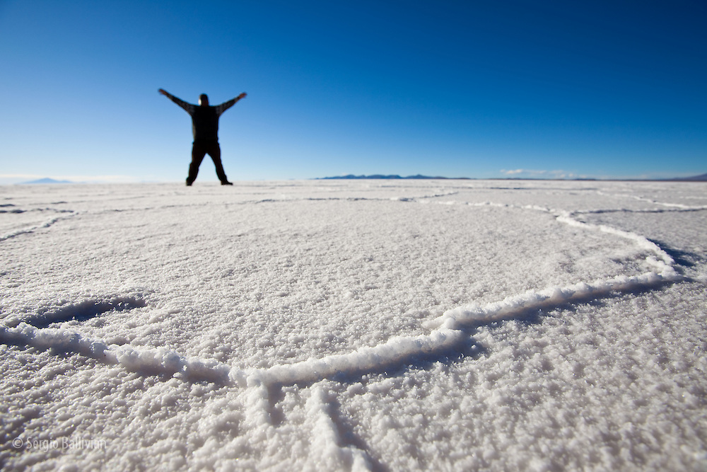 A tourist walks on the crusty salt layer of the Salar de Uyuni in Bolivia's Altiplano. The Salar de Uyuni is the world's largest salt flat at over 10,000 sq. kilometers lying at 12,000 ft asl. between two massive ranges of the Andes mountains.