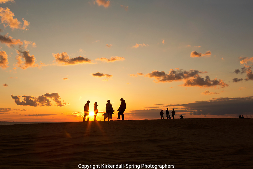 NC01429-00...NORTH CAROLINA - Watching the sunset from a tall sand dune, a popular activity at Jockey's Ridge State Park on the Outer Banks at Nags Head.