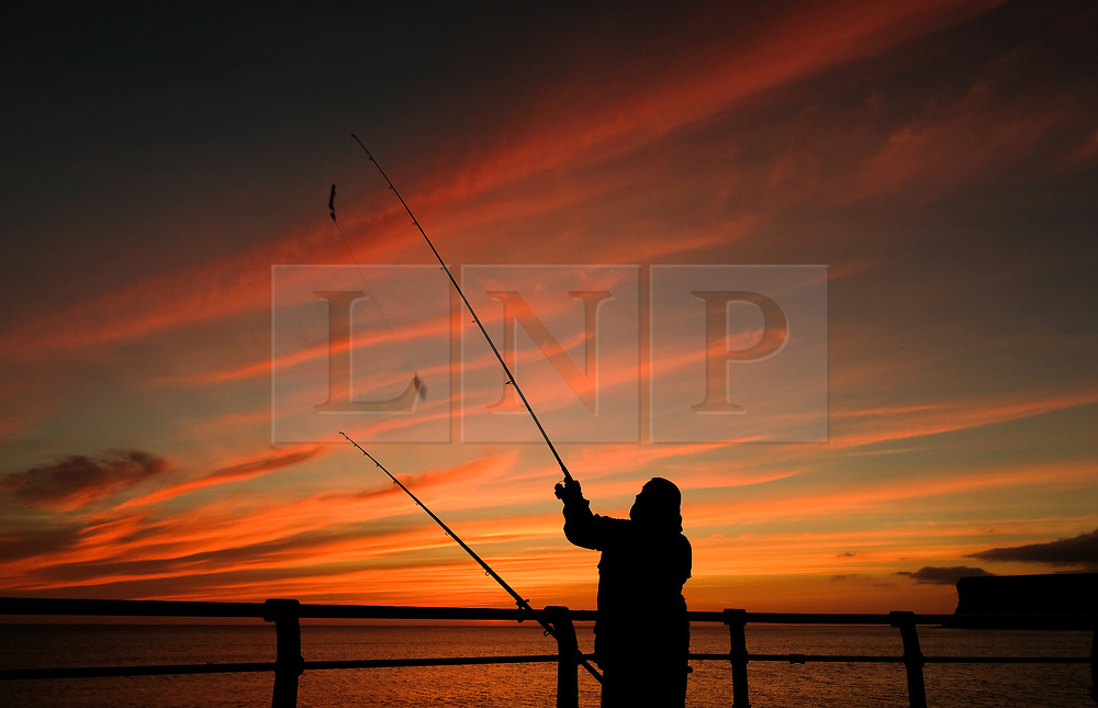 © Licensed to London News Pictures. <br /> 11/08/2017. <br /> Saltburn by the Sea, UK.  <br /> <br /> A fisherman casts from the end of the pier at sunrise in the North Yorkshire coastal town of Saltburn by the Sea.<br />   <br /> Photo credit: Ian Forsyth/LNP