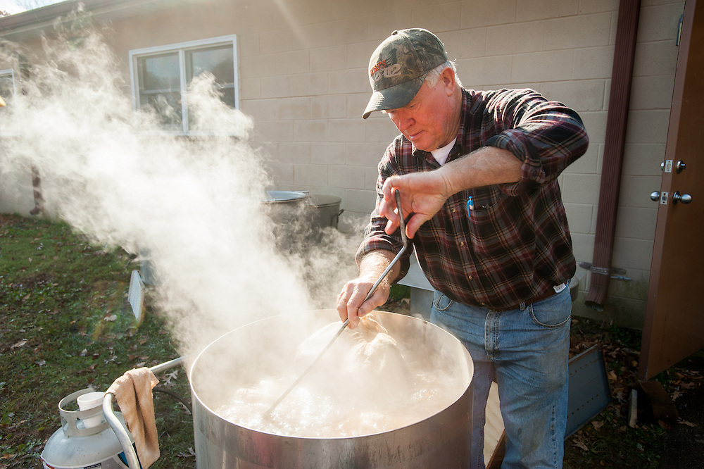 Man boiling stuffed hams outside, in large pans in St Mary's County, Maryland, USA