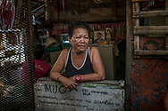 """Rosita """"Rose"""" Opiasa, 59, whose son, Jayson Rivera, 32, was slain in the drug war, remains pro-Duterte, rare in Market 3 slum where she lives.  Jayson's photograph can be seen in the background.  Rose runs this corner shop where she sells single cigarettes or various small portions of shampoo, detergent, etc. because her slum-dwelling clients cannot afford larger portions.  Navotas, Metro Manila, Philippines."""