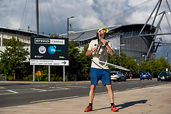 MANCHESTER, ENGLAND - Thursday, July 2, 2020: A man hula hoops whilst playing the saxophone outside Manchester City's City of Manchester Stadium before the FA Premier League match between Manchester City FC and Liverpool FC. The game was played behind closed doors due to the UK government's social distancing laws during the Coronavirus COVID-19 Pandemic. This was Liverpool's first game as Premier League 2019/20 Champions. (Pic by Propaganda)