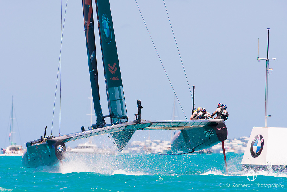 The Great Sound, Bermuda, 18th June. Oracle Team USA round the top mark behind Emirates Team New Zealand in race three on day two of the America's Cup.