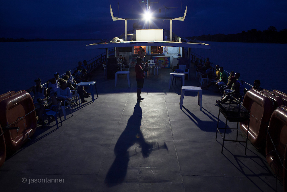 A young local man entertains fellow locals with his talens playing the trumpet on the entertainment deck of the Avenger. The Avenger III is a passenger ship making the twice a month journey from the frontier town of Tabatinga in the Tr&ecirc;s Fronteiras region of Northwestern Brazil, to the capital of the State of Amazonas, Manaus. It&rsquo;s also where the Rio Amazonas enters Brazil from its source in neighboring Peru. <br /> <br /> Carrying passengers and crew totaling almost 200 and small cargo, the ship meanders its way along the Rio Amazonas and Rio Solimoes for four days and three nights. Stopping at half a dozen or so makeshift ports en-route, the service provides a vial link for communities along the river to get products to the city and more importantly, in the absence of roads or airfields, provide a means for the sick to reach care in the city of Manaus.<br /> <br /> For those not fortunate to be accommodated in one of the two or three cabins available, home is space found for a self supplied hammock amongst the kaleidoscopic web of coloured fabrics. <br /> <br /> By the second day, negotiating a stroll from port to starboard can seem more like negotiating an assault course of tangled ropes and personal baggage deliberately piled high to protect ones personal space.<br /> <br /> Food served three times daily is adequate, a staple of soups, chicken, rice and noodles. An &lsquo;entertainment&rsquo; deck on the top floor provides ample opportunity to be social engaging in card and board games with beer swilling, chain smoking locals.