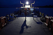 A young local man entertains fellow locals with his talens playing the trumpet on the entertainment deck of the Avenger. The Avenger III is a passenger ship making the twice a month journey from the frontier town of Tabatinga in the Três Fronteiras region of Northwestern Brazil, to the capital of the State of Amazonas, Manaus. It's also where the Rio Amazonas enters Brazil from its source in neighboring Peru. <br /> <br /> Carrying passengers and crew totaling almost 200 and small cargo, the ship meanders its way along the Rio Amazonas and Rio Solimoes for four days and three nights. Stopping at half a dozen or so makeshift ports en-route, the service provides a vial link for communities along the river to get products to the city and more importantly, in the absence of roads or airfields, provide a means for the sick to reach care in the city of Manaus.<br /> <br /> For those not fortunate to be accommodated in one of the two or three cabins available, home is space found for a self supplied hammock amongst the kaleidoscopic web of coloured fabrics. <br /> <br /> By the second day, negotiating a stroll from port to starboard can seem more like negotiating an assault course of tangled ropes and personal baggage deliberately piled high to protect ones personal space.<br /> <br /> Food served three times daily is adequate, a staple of soups, chicken, rice and noodles. An 'entertainment' deck on the top floor provides ample opportunity to be social engaging in card and board games with beer swilling, chain smoking locals.