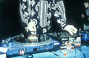 A man in a black and white patterned shirt, DJing, UK 2000's