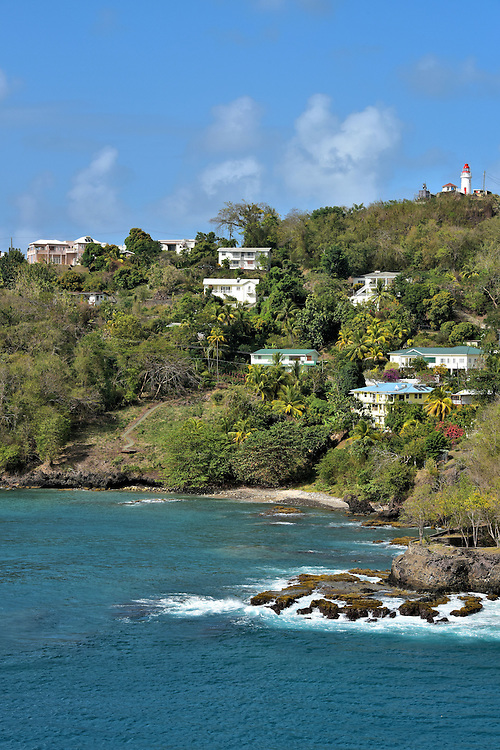 Vigie Lighthouse Near Castries, Saint Lucia<br /> The Vigie Lighthouse was established in 1883. The current white, cylindrical tower with a red lantern was rebuilt in 1915. This light still serves a critical role in managing the harbor at the capital city of Castries. The keeper coordinates the arrival and departure of major ships and dispatches the assistance of tug boats when needed.