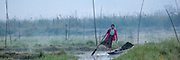 Woman farmer rowing flat boat with leg through misty morning floating farm