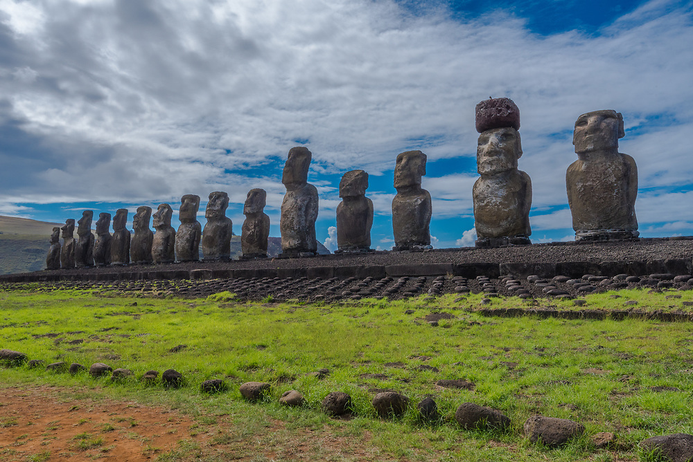 Wide angle shot of 15 Moai statues facing inward over Easter Island at Tongariki with a dramatic white cloud and blue sky background.