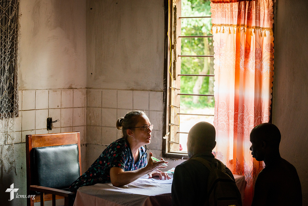 Donna Mulholland, a member of Shepherd of the Valley Lutheran Church, Fort Bridger, Wyo., talks with a patient in the intake area of the clinic on the first day of the LCMS Mercy Medical Team on Monday, May 7, 2018, in the Yardu village outside Koidu, Sierra Leone, West Africa. LCMS Communications/Erik M. Lunsford