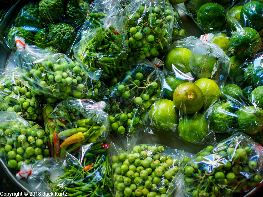 20 JUNE 2018 - BANGKOK, THAILAND:  Produce including aubergine, chilies, and citrus in plastic bags at Makkasan Market, a small local market in central Bangkok. Officials in Thailand are wrestling with Thais use of plastic bags. The issue became a public one in early June when a whale in Thai waters died after ingesting 18 pounds of plastic. In a recent report, Ocean Conservancy claimed that Thailand, China, Indonesia, the Philippines, and Vietnam were responsible for as much as 60 percent of the plastic waste in the world's oceans.    PHOTO BY JACK KURTZ