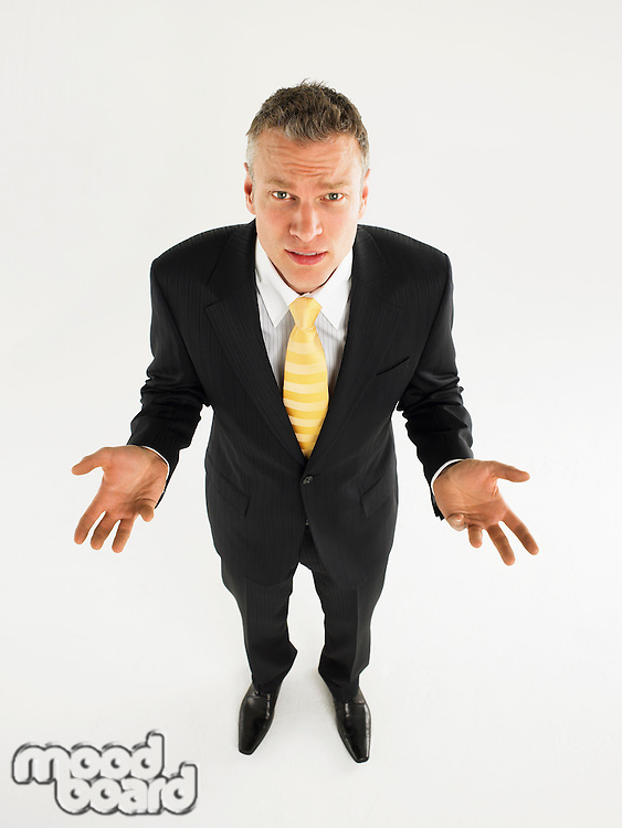 Man in suit with palms raised full length