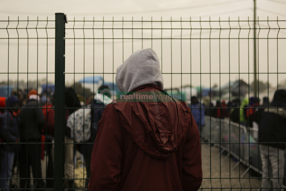 October 24, 2016 - Calais, Nord-Pas-de-Calais-Picardie, France - A refugee from the outside camp looks inside the official camp. The French state has started processing the inhabitants of the Jungle refugee camp in Calais and distribute them to centres around France. Not all of the 6 to 10 thousand refugees living in the Jungle (according to different estimates) are expected to leave voluntarily and some have already disappeared. (Credit Image: © Michael Debets/Pacific Press via ZUMA Wire)