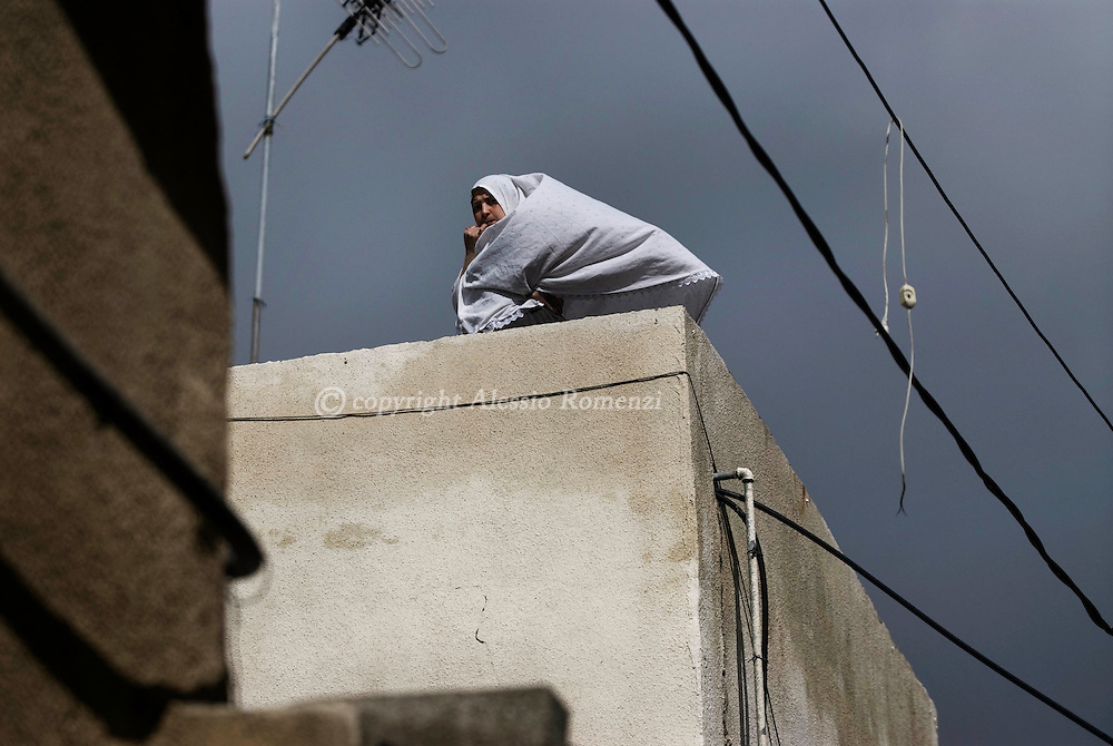 JERUSALEM : A Palestinian woman stands on a roof during clashes near the Al-Aqsa mosque compound in Jerusalem's old city on February 28, 2010. Clashes broke out at Jerusalem's flashpoint Al-Aqsa mosque compound on Sunday after police entered to arrest Palestinians who had hurled rocks at visitors they believed were Jewish extremists..© ALESSIO ROMENZI