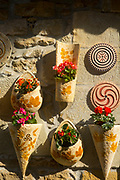 SANTILLANA DEL MAR, SPAIN - April 20 2018 - Stone wall and plant pots with springtime flowers hanging in town centre of Santillana del Mar, Cantabria, Spain.