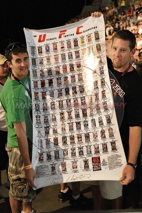 LAS VEGAS, NEVADA, JULY 10, 2009: Fans pose with an autographed poster listing all UFC events to date before the weigh-in for UFC 100 inside the Mandalay Bay Events Center in Las Vegas, Nevada
