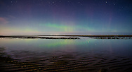 The northern lights glow over and reflect in the still waters of Cape Cod Bay.