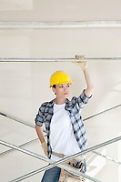 Front view of mid adult worker looking away while standing under scaffold