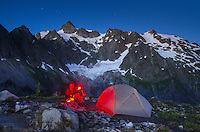 Hiker with red headlamp at backcountry camp on ridge above Lake Ann, Mount Shuksan in the background, Mount Baker Wilderness North Cascades Washington