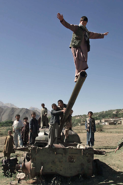 20010929-RUHA, AFGHANISTAN: Afghan children play at the destroyed tank in the village Ruha in Pahjshir valley, territory controlled by the anti-Taliban Northern Alliance, Saturday, 29 September, 2001.