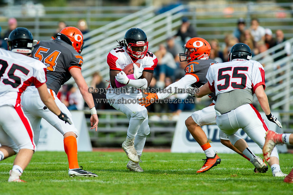 KELOWNA, BC - OCTOBER 6:  Andre Goulbourne #21 of the VI Raiders holds the ball tight as Mitch Walz #31 and Cory McCoy #54 of Okanagan Sun move in for the tackle during BCFC regular season at the Apple Bowl on October 6, 2019 in Kelowna, Canada. (Photo by Marissa Baecker/Shoot the Breeze)