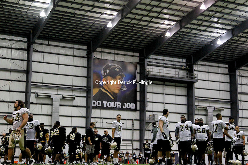 July 27, 2012; Metairie, LA, USA; A sign of New Orleans Saints head coach Sean Payton who was suspended by NFL commissioner Roger Goodell is seen over players following a training camp practice at the team's indoor practice facility. Mandatory Credit: Derick E. Hingle-USA TODAY SPORTS