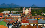 The colorful 18th century El Calvario Church rises above the rooftops of Leon, and the very active Cerro Negro Volcano rises in the background.
