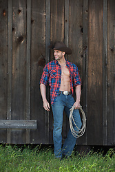 Rugged muscle cowboy with an open shirt on a ranch