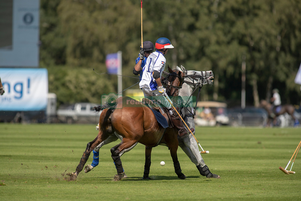 La Dolfina (in white) take on Park Place (in blue) in the Out-Sourcing Royal Windsor Cup final at the Guards Polo Club, Windsor Great Park, Egham, Surrey.