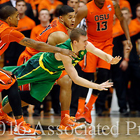 Oregon's Casey Benson, center, loses control of the ball while being guarded by Oregon's Gary Payton II, left, and Malcolm Duvivier, rear, in the second half of an NCAA college basketball game, in Corvallis, Ore., on Sunday, Jan. 3, 2016. Oregon State won 70-57. (AP Photo/Timothy J. Gonzalez)