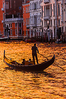 A gondolier rowing his gondola along the Grand Canal at sunset, Venice, Italy.