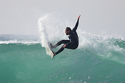 ©2020 Tom Nicholson. 23/04/2020. Padstow, UK. A surfer catches a wave this afternoon near Padstow on the north coast of Cornwall. A period of warm weather is set to continue for the rest of the week. Photo credit : Tom Nicholson