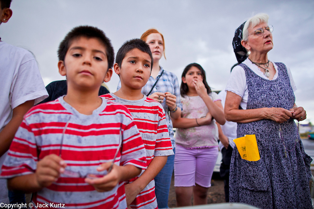 July 22 - PHOENIX, AZ: People participate in a rosary service on a street corner in Phoenix. About 50 people gathered on a street corner in a Hispanic neighborhood in Phoenix, AZ, Thursday night to pray the rosary. They are members of a Catholic community that opposes Arizona's tough new immigration law, SB 1070, which requires local police officers to check the immigration status of people they suspect of being in the US illegally and requires legal immigrants in Arizona to carry their immigration documents with them at all times. Photo by Jack Kurtz