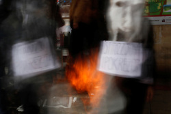 Students in grotesque masks symbolically burn copies of Ir-Realta newspaper during a protest against censorship on the university campus..