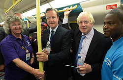Celebration of the 2012 Olympic Games volunteering one year on. <br /> (L-R) Prime Minister of the United Kingdom David Cameron and Mayor of London Boris Johnson on the London Underground on their way to the Queen Elizabeth Olympic Park.<br /> Mayor of London Boris Johnson and Lord Coe will be taking to the stage at Go Local to encourage a new drive in volunteering one year on from the Games. Also present are multi-platinum selling pop rock band McFly; world famous comedian Eddie Izzard, Brit Award nominated The Feeling, and Britain's Got Talent winners Attraction, in addition to stars Jack Carroll and Gabz. The event will be the UK's biggest ever celebration of volunteering and first Olympic and Paralympic legacy event at Queen Elizabeth Olympic Park.<br /> London, United Kingdom<br /> Friday, 19th July 2013<br /> Picture by Andrew Parsons / i-Images