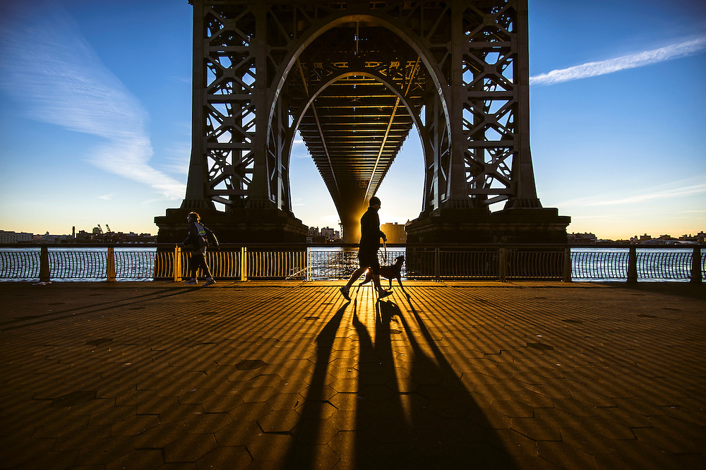 A jogger passes down the Williamsburg Bridge at sunrise, New York