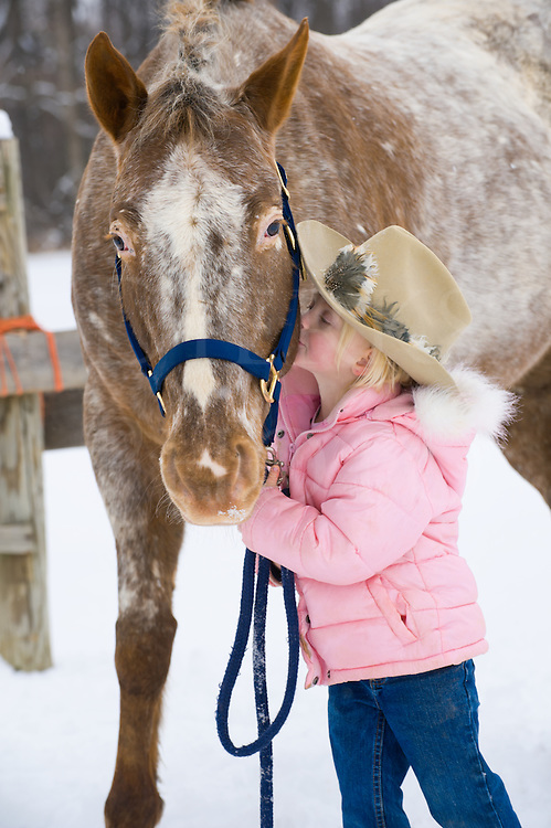 Little blonde girl kissing big Appaloosa horse outdoors in snow, close up of preschooler wearing pink winter coat and cowboy hat with Princess, who is a good sport with the kids as always, Pennsylvania, PA, USA.