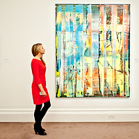 A Sotheby's employee poses in front of a painting entitled 'Abstraktes Bild (769-1)' by Gerhard Richter (Est £ 7.5-9.5 million) during the press preview of the Sotheby's forthcoming February sales of Impressionist & Modern Art and Contemporary Art in London, including works by Picasso, Bacon, Monet, Richter, Miró, Basquiat.