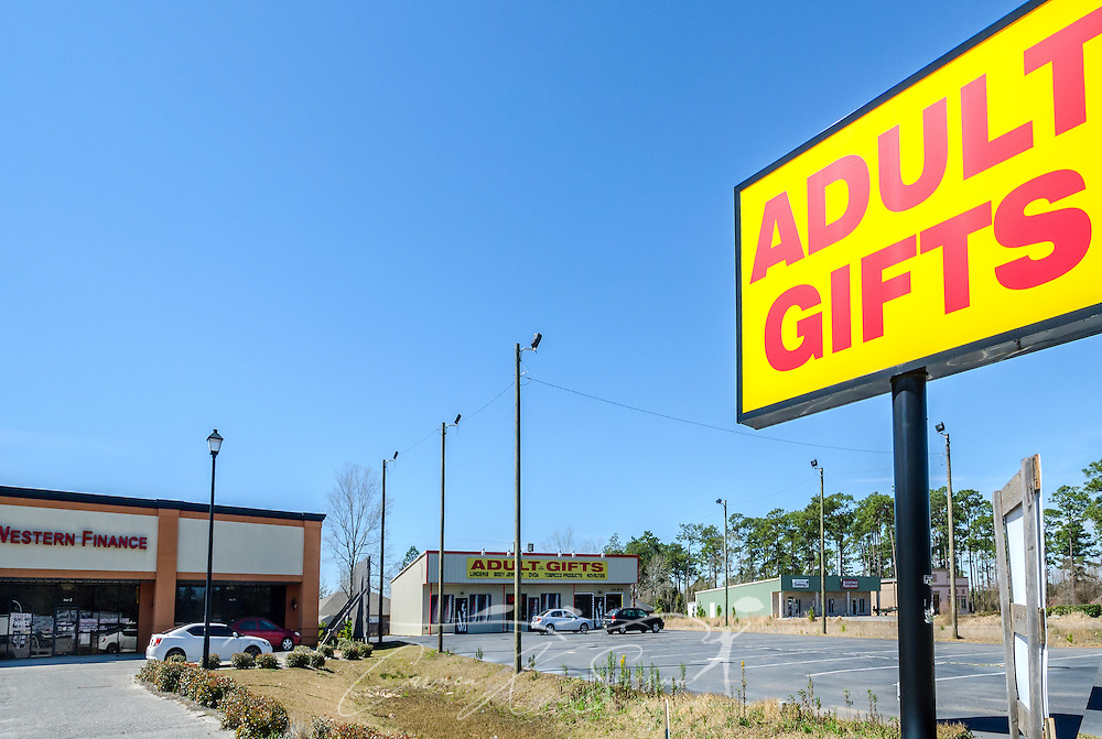 """A sign advertises an adult gifts store, March 6, 2016, in Foley, Alabama. Day care owner Deborah Stokes opened Kids' Space day care in the strip mall adjacent to the adult-themed shop in 2011. Alabama state law prohibits adult stores from opening within 1,000 feet of a day care, but there are no laws preventing a day care from opening beside an adult store. The day care, now closed, is one of several Stokes has opened over the past few years. Alleged problems and violations have brought the day cares under scrutiny, with critics saying that because the businesses operate as Christian day cares, they slip through a """"religious loophole"""" that allows them to bypass the licensing and safety standards required of non-Christian day cares. Stokes now operates another day care, Little Nemo's, in Spanish Fort, Alabama. (Photo by Carmen K. Sisson/Cloudybright)"""