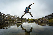 A hiker jumps over an alpine pond in the White Pass.