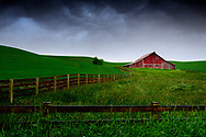 Red barn in Palouse with stormy skies overhead