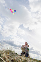 Father and daughter (5-6) flying kite on dunes