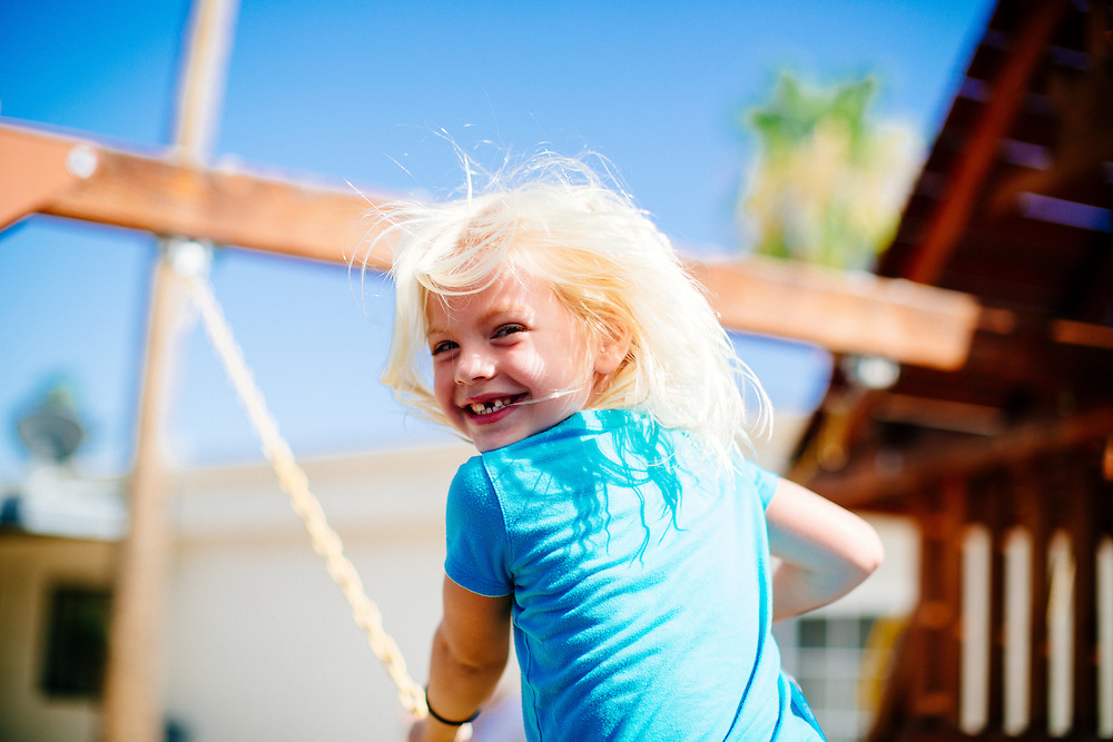 Little girl smiles back at the camera while swinging on backyard swingset