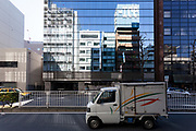 A delivery van in front of apartment and office building reflected in a glass building-front. Yokohama, Kanagawa, Japan. Friday November 23rd 2018